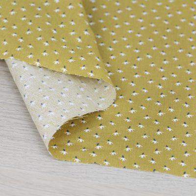 Tessuto in cotone con soffioni su fondo giallo