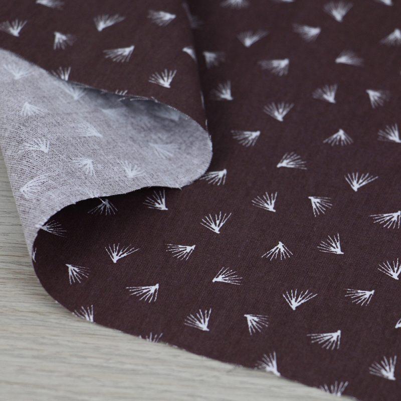 Tessuto in cotone con ciuffetti su fondo prugna