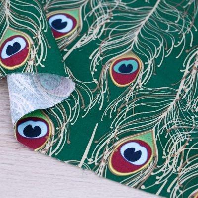 Tessuto in cotone Gütermann Elegant Spirit con piume di pavone a fondo verde