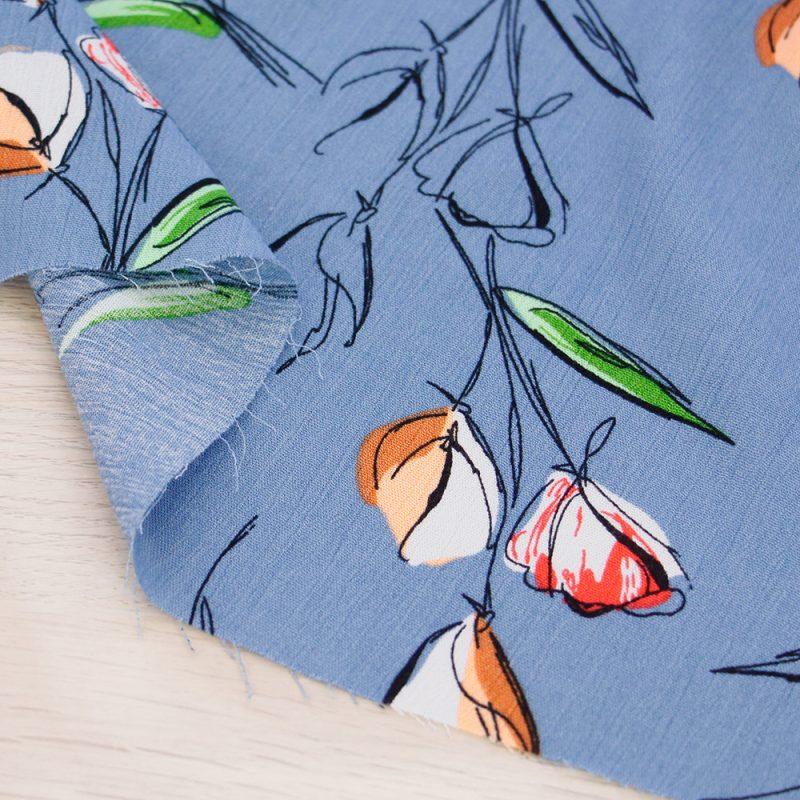 Tessuto crepe di viscosa a fiori con fondo azzurro