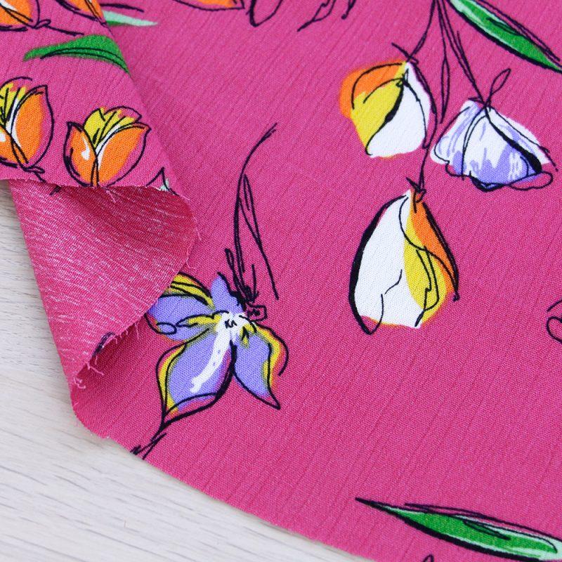 Tessuto crepe di viscosa a fiori con fondo fucsia