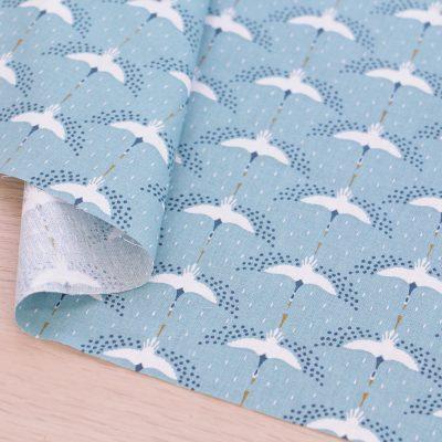 Tessuto in cotone con aironi su fondo azzurro