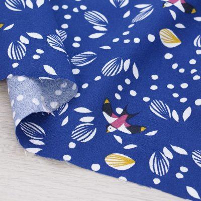 Tessuto in viscosa con rondini su fondo blu